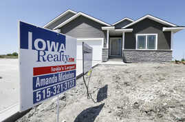 A sign sits in front of a new home for sale in West Des Moines, May 21, 2014, Iowa.