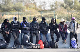 "FILE - Young migrants wait to board a bus leaving for a reception centre, in Calais, on Oct. 28, 2016, following a massive operation to clear the ""Jungle"" migrant camp."