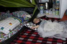 FILE - Yaldof Natzafi, a 1 year -old Afghan baby girl, sleeps at a make shift tent at the west terminal of an abandoned old airport which is used as a shelter for thousands of migrants, in southern Athens, Monday, June 20, 2016.