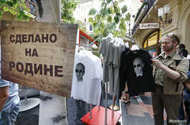 "FILE - T-shirts, displaying images of Russia's President Vladimir Putin, are on sale at GUM department store in central Moscow, June 11, 2014. The sign reads ""Made in Fatherland""."