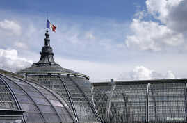 A view shows a French flag flying half-mast at the Grand Palais in Paris July 28, 2014. French President announced three days of mourning and ordered that flags on government buildings across France fly at half-mast for three days from Monday after t