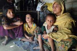 """Habiba, 32, and her three children at a Rohingya village in Bangladesh. According to the Rohingya woman, she was raped by a Burmese soldiers and a Mogh, after her husband was beaten up and taken away from her village in Rakhine in December. """"They loo..."""