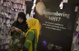 Shoppers take a photo next to prayer notes for passengers aboard Malaysia Airlines Flight 17 at a shopping mall in Kuala Lumpur, Malaysia, Thursday, July 24, 2014. The crash of the Malaysian passenger plane over eastern Ukraine a week ago killed all