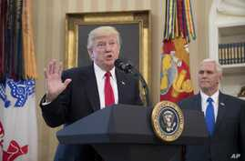 President Donald Trump, accompanied by Vice President Mike Pence, right, speaks during a signing ceremony for executive orders regarding trade in the Oval Office at the White House, March 31, 2017, in Washington.