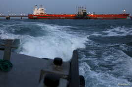 Oil gets pumped into a tanker docked at a PDVSA industrial complex in the northeastern state of Anzoategui, April 15, 2015. Many foreign ports won't accept tanks with oil-slicked hulls, and hand cleaning delays oil shipments vital to Venezuela's econ