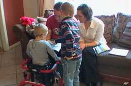 Josh Tolboe, 3, (left) was diagnosed with spina bifida and gets around in a red walker