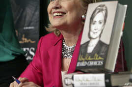 """HiIlary Rodham Clinton listens before signing a copy of her book, """"Hard Choices"""" at Barnes and Noble bookstore in New York, June 10, 2014."""