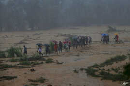 Sri Lankan onlookers walk towards safety during a minor land slide following heavy rains in Elangipitiya village in Aranayaka about 72 kilometers (45 miles) north east of Colombo, Sri Lanka, Wednesday, May 18, 2016.