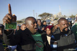 Mineworkers dance as they gather for check-ins near Lonmin's Marikana platinum mine before returning to work in South Africa, June 25, 2014.