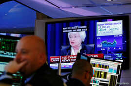 Traders work as Federal Reserve Chair Janet Yellen speaks on a television above the floor of the New York Stock Exchange (NYSE) shortly after the opening bell in New York City, U.S., June 15, 2016