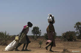 FILE - Women carry food at a food distribution site in Nyal, Unity State.  More than one million people have been forced from their homes by the conflict, of which 803,200 have been displaced within South Sudan and 254,600 have fled to neighbouring c
