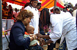 Newly re-elected president Blaise Compaore's wife Chantal holds a young boy during the launch of a new vaccination campaign against meningitis in Ouagadougou, Burkina Faso, 06 Dec. 2010