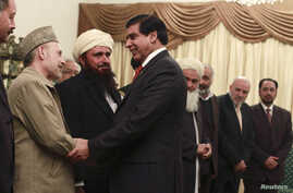 Pakistan's Prime Minister Raja Pervez Ashraf (R) shakes hands with members of Afghanistan's High Peace Council at the prime minister's residence in Islamabad November 12, 2012.