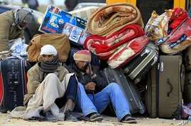 Egyptians sit next to their belongings as they wait for transportation near the Libyan and Tunisian border crossing of Ras Jdir after fleeing unrest in Libya, February 28, 2011
