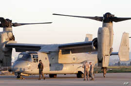 US Marine  officers work next to an MV-22 Osprey vertical take off and lift aircraft , in the Sigonella airbase, Sicily, Thursday, March 24, 2011. (AP Photo/Andrew Medichini)