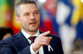 FILE - New Slovak Prime Minister Peter Pellegrini gestures as he arrives at a European Union summit in Brussels, Belgium, March 22, 2018.