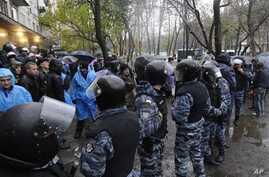 Riot police separate opposition and pro-government activists outside an election precinct in Kiev where the opposition alleged election fraud in Kiev, Ukraine, November 2, 2012.