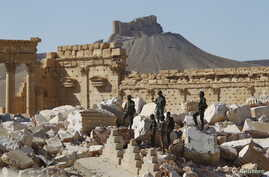 Syrian army soldiers stands on the ruins of the Temple of Bel in the historic city of Palmyra, in Homs Governorate, Syria, April 1, 2016. The Fakhreddin's Castle is seen in the background.