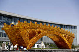 Workers install wires on a Golden Bridge of Silk Road structure outside the National Convention Center, the venue for the Belt and Road Forum for International Cooperation, in Beijing, April 18, 2017. Starting Sunday, Vladmir Putin of Russia, Recep T...