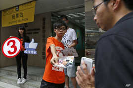 Joshua Wong, a student leader in the Occupy Central movement handouts leaflets near a polling station to urge people to vote on the last day for an unofficial referendum on democratic reform in Hong Kong, June 29, 2014.
