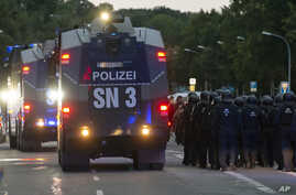 """A police water cannons passes by a far-right protest in front of a Karl Marx monument in Chemnitz, Germany, Monday, Aug. 27, 2018 after a man has died and two others were injured in an altercation between several people of """"various nationalities"""" in"""