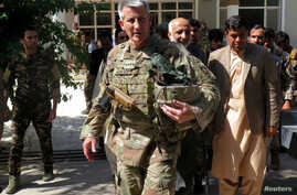 U.S. Army General John Nicholson, commander of Resolute Support forces and U.S. forces in Afghanistan, walks with Afghan officials during an official visit in Farah province, Afghanistan, May 19, 2018.