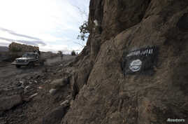 FILE - Shi'ite Houthi rebels drive a patrol truck past a Ansar al-Sharia flag painted on the side of a hill, along a road in Almnash, the main stronghold of Ansar al-Sharia, in Rada, Nov. 22, 2014.
