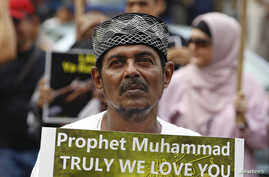 A Muslim protester holds up a sign during a protest against an anti-Islam film made in the U.S. mocking the Prophet Mohammad, outside the U.S embassy in Jakarta September 21, 2012.  REUTERS/Enny Nuraheni  (INDONESIA - Tags: CIVIL UNREST RELIGION)