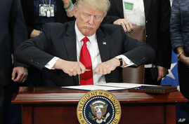 FILE - President Donald Trump takes the cap off a pen before signing an executive order on immigration during a visit to the Homeland Security Department in Washington, Jan. 25, 2017. Following recent terror attacks in London, Trump has renewed calls