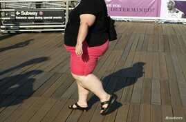FILE - A woman walks along a boardwalk in New York. Lifestyle and lack of access to healthcare have been among the factors attributed to a rise in the mortality rate of white women in the United States.
