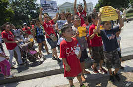 Demonstrators march following a news conference of immigrant families and children's advocates responding to President Barack Obama's position on the crisis of unaccompanied children and families illegally entering the US, in front of the White House