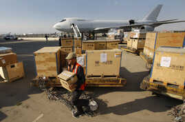 FILE - A worker carries a box with U.N. equipment at the Damascus airport in Syria, May, 8, 2012.