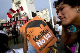 A man holds a sign during a protest against presidential candidate Keiko Fujimori and against the 1992 coup by her father, former President Alberto Fujimori, in downtown Lima, Peru, Tuesday, April 5, 2016.