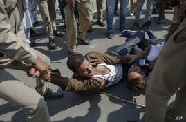 Indian policemen detain Kashmiri Shiite Muslims for participating in a religious procession in central Srinagar, Indian controlled Kashmir, Wednesday, Sept. 19, 2018.