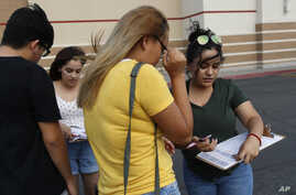 FILE - Activists Maria Nieto, right, and Alma Romo, second from left, register people to vote in the U.S. midterm election in November, in Las Vegas, Neveda, Aug. 15, 2018.