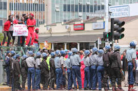 Zimbabwean police officers keep an eye on opposition party supporters as they prepare to march during a protest aimed at President Robert Mugabe in Harare, Zimbabwe, March, 14, 2016.