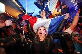 Supporters of far-right candidate Marine Le Pen, celebrate in Henin-Beaumont, northern France, after exit poll results of the first round of the presidential election are announced, April 23, 2017.