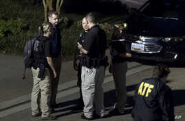 Agents with the Bureau of Alcohol, Tobacco, Firearms and Explosives leave the family home, in Baltimore, Sunday, Aug. 26, 2018, of the suspect in a mass shooting earlier in the day in Jacksonville, Florida.