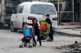 Children push containers in strollers as they flee deeper into the remaining rebel-held areas of Aleppo, Syria, Dec. 12, 2016.