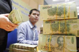FILE - Stacks of 100,000 Vietnamese Dong notes ($4.70) are pictured as employees count money at a branch of the Bank for Investment and Development of Vietnam (BIDV) in Hanoi, Jan. 20, 2014.