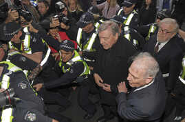 Cardinal George Pell, center right, is surrounded by police as he arrives at the Melbourne Magistrates Court in Melbourne, Australia, July 26, 2017.