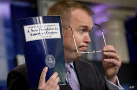 Budget Director Mick Mulvaney holds up a copy of President Donald Trump's proposed fiscal 2018 federal budget as he speaks to members of the media in the Press Briefing Room of the White House in Washington, May 23, 2017.