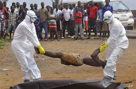 Health workers places the body of a man, inside a plastic body bag as he is suspected of dying due to the Ebola virus as people, rear, look on in Monrovia, Liberia, Thursday, Sept. 4, 2014.  (AP Photo/Abbas Dulleh)