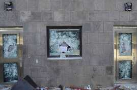 """Anything but the messenger of God,"" reads a sign left in the shattered window of a U.S. compound after it was stormed by rioters in Sana'a, Yemen, Sept. 13, 2012."