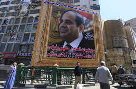 People stand under a huge banner of Egypt's former army chief Abdel Fattah al-Sisi in downtown Cairo, March 27, 2014.