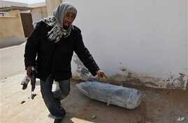 Anti-Gadhafi rebel in front of an unexploded bomb from an air strike by Gadhafi's warplanes, in the town of Ras Lanouf, eastern Libya, March 8, 2011