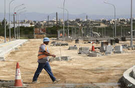A worker passes inside the construction of a crossing point that will link ethnically divided Cyprus' breakaway Turkish Cypriot north and internationally recognized south in Dherynia, April 27, 2017.