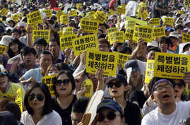 South Koreans shout slogans during a rally demanding the adoption of a special law for the sunken ferry Sewol in Seoul, South Korea, Friday, Aug. 15, 2014. Before Mass got under way, Francis met privately with about a dozen survivors of South Korea's