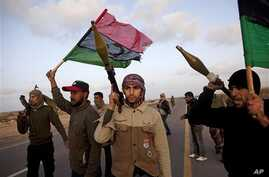 Libyan rebels who are part of the forces against Libyan leader Moammar Gadhafi stand on a road as they secure an area outside the village of Bin Jawwad, west of the recently captured oil town of Ras Lanuf, eastern Libya, March 5, 2011