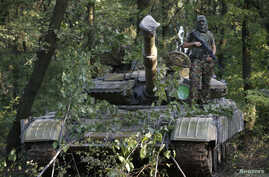 A pro-Russian separatist poses for a picture atop a T-64 tank in Donetsk, eastern Ukraine, July 16, 2014.